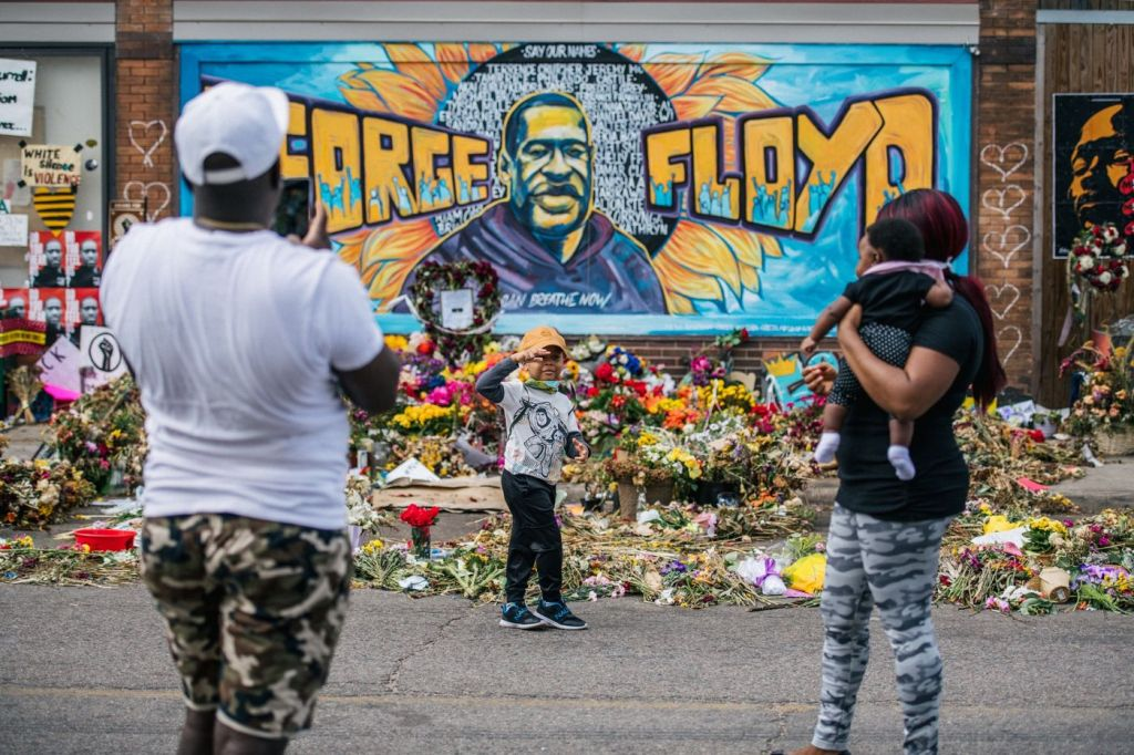 A family takes photos in front of a mural of George Floyd in Minneapolis on June 10. Photographer: Brandon Bell/Getty Images North America